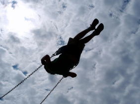 Scuse me while I kiss the sky. Silhouette of person in a swing.